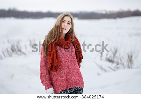 portrait of cute attractive young blond serious girl with red sweater and scarf looking to camera and walking on natural grey cloudy background in countryside field. Winter outdoor photo - stock photo