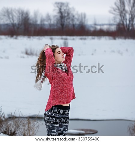 portrait of cute attractive young girl with ling hair with black and white trousers red sweater on natural background. Winter outdoor photo in cloudy weather  - stock photo