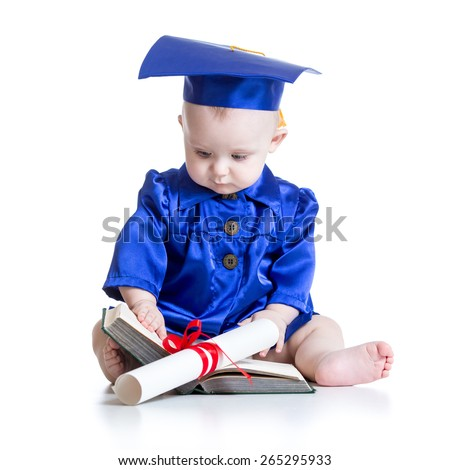 Portrait of cute baby boy in academic costume with book and scroll