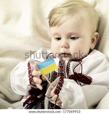 portrait of cute baby boy in national costume playing with ucrainian flag, toned