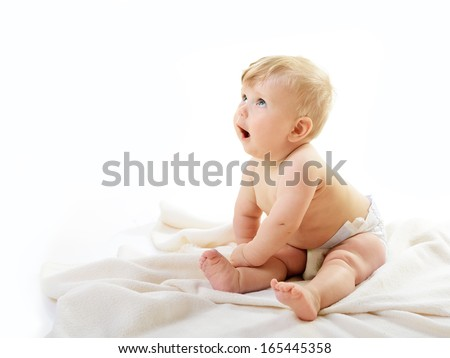 Portrait of cute baby boy look up sitting on plaid, adorable child closeup - stock photo