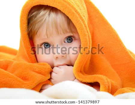 portrait of cute baby boy lying on orange plaid and sucking his finger