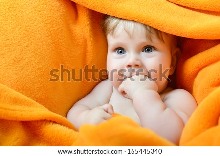portrait of cute baby boy lying on orange plaid and sucking his finger - stock photo