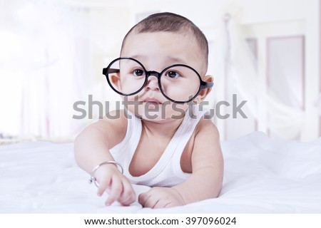 Portrait of cute baby boy lying on the bedroom while wearing glasses and looking at the camera - stock photo