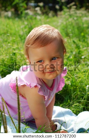 portrait of cute baby girl crawling on the grass - stock photo