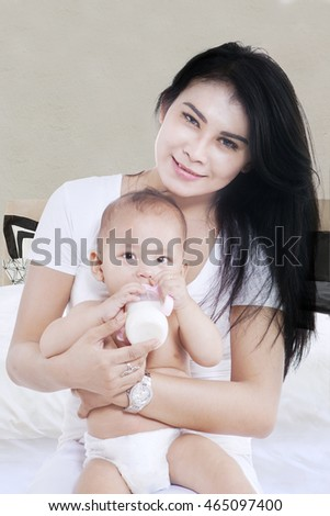 Portrait of cute baby girl drinking a milk from bottle in the mom's arms on the bedroom