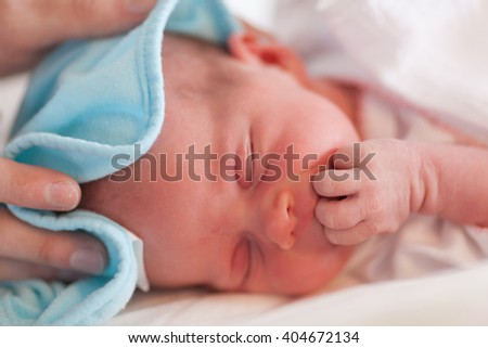 Portrait of cute baby girl eating fingers on changing table. - stock photo