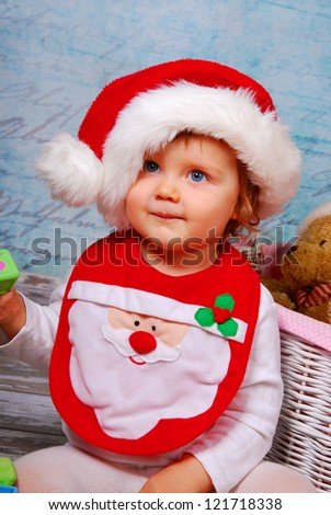 portrait of cute baby girl in red santa hat playing with toys - stock photo