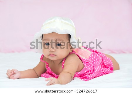Portrait of cute baby girl on the bed.