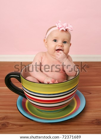 Portrait of cute baby girl sitting inside a giant tea cup or mug