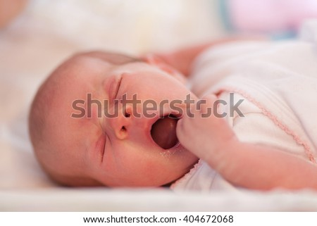 Portrait of cute baby girl yawning on changing table.