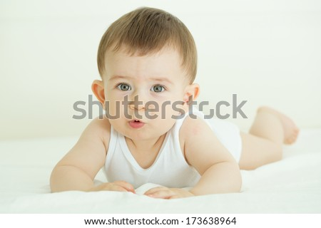 Portrait of cute baby in bed, lying on his belly and looking at the camera with interest. Indoors shot. - stock photo