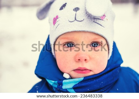 Portrait of cute baby in winter park  - stock photo