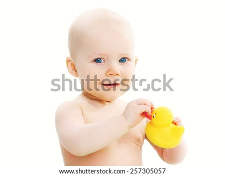 Portrait of cute baby playing with yellow rubber duck