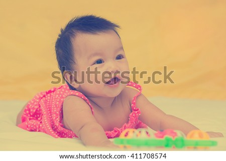 Portrait of cute baby smiling girl on the bed with toy. vintage style - stock photo