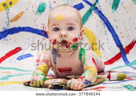 portrait of cute baby with brushes, smeared with paints, gouache paints - stock photo