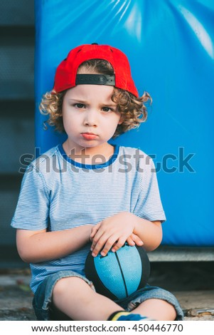 Portrait of cute basketball player in red cap with ball sitting and looking at camera