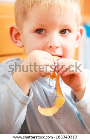 Portrait of cute blond child boy kid preschooler eating apple peel. Healthy diet and nutrition. At home.