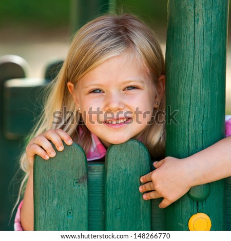 Portrait of cute blond girl holding on to wooden fence. - stock photo