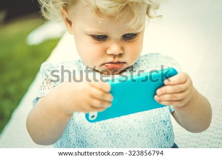 Portrait of cute blonde baby girl with smartphone. Toned image - stock photo