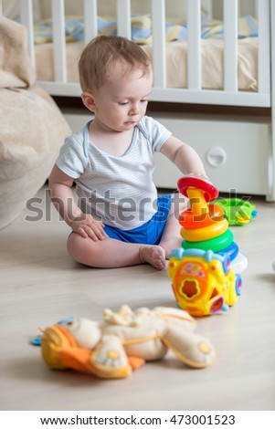 Portrait of cute boy assembling colorful pyramid on floor at living room