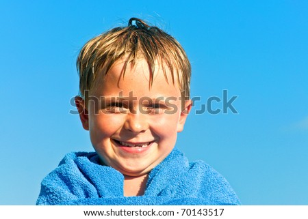 portrait of cute boy at the beach with towel - stock photo