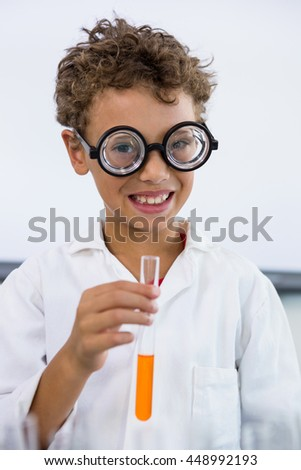 Portrait of cute boy holding test tube with liquid at laboratory