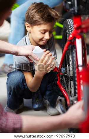 Portrait of cute boy lubricating bicycle chain in garage