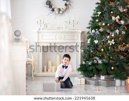 Portrait of cute boy near the christmas tree - stock photo