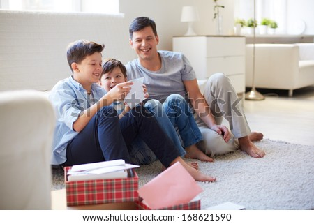 Portrait of cute boy opening envelope with his father and brother near by at home - stock photo