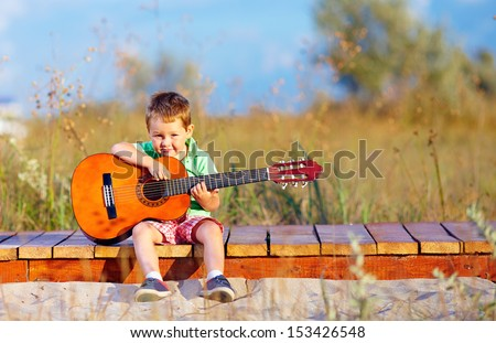 portrait of cute boy playing a guitar on summer field - stock photo