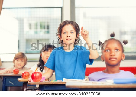 Portrait of cute boy raising hand at workplace with his classmates behind.