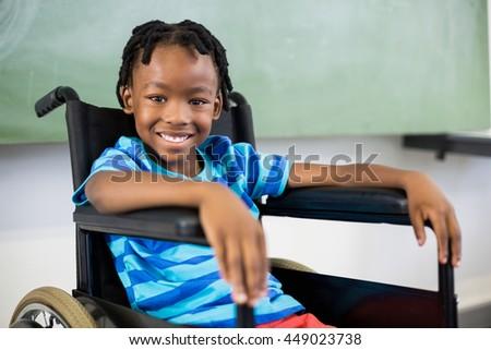 Portrait of cute boy sitting on wheelchair on school - stock photo