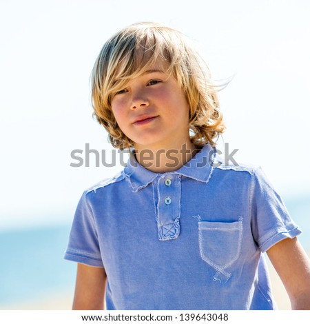 Portrait of cute boy wearing blue polo shirt outdoors.