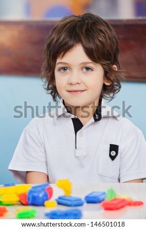 Portrait of cute boy with blocks on desk at kindergarten - stock photo