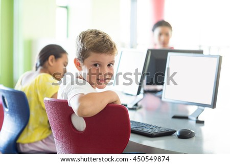 Portrait of cute boy with classmates and teacher in computer room - stock photo