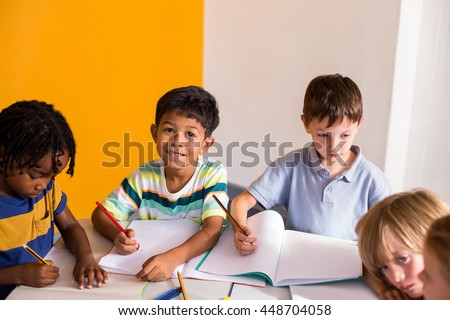 Portrait of cute boy with classmates in classroom
