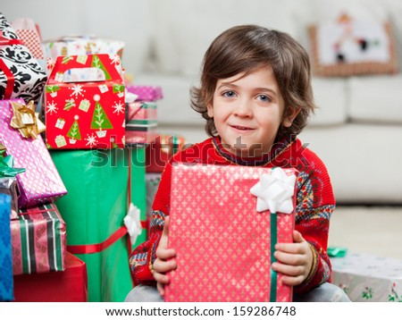 Portrait of cute boy with holding Christmas present at home - stock photo