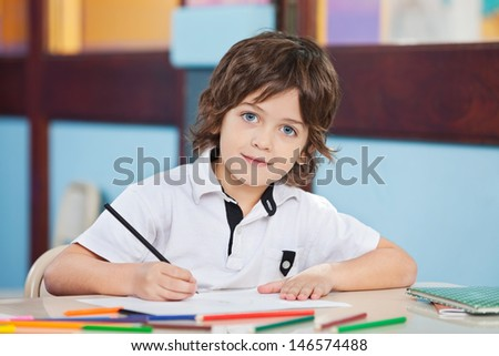 Portrait of cute boy with sketch pen and paper at desk in classroom - stock photo