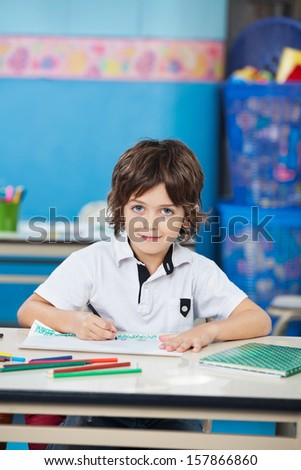 Portrait of cute boy with sketch pen drawing in classroom - stock photo