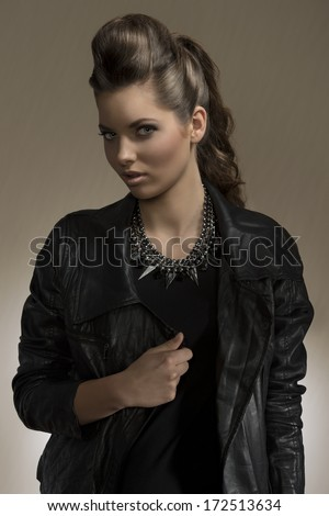 portrait of cute brunette girl with long wavy hair and fashion casual style. wearing leather jacket and rock necklace   - stock photo