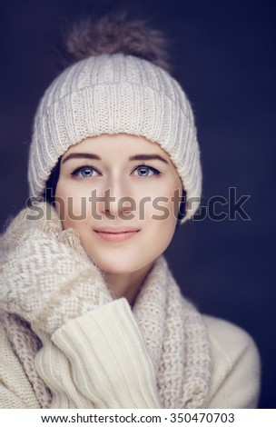 Portrait of cute brunette woman in white pulover and winter hat.