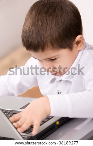Portrait of cute caucasian boy with laptop