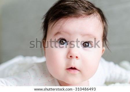 Portrait of cute caucasian newborn baby girl in spotted romper suit looking with beautiful hazel brown eyes and curious glance, lying on woolen blanket on bed at home. The depth of field is short.