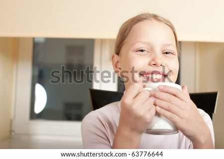 Portrait of cute cheerful little girl with big white cup. Drinking tea. - stock photo