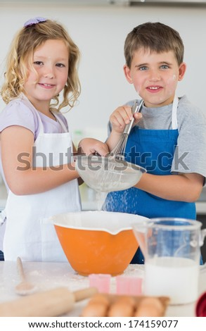 Portrait of cute children baking cookies together in kitchen