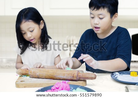 Portrait of cute children playing colourful clay toy together with rolling dough and wooden board at home