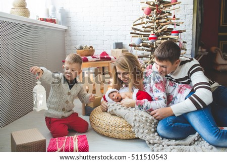 Portrait of cute couple and their babies near fashion xmas tree.