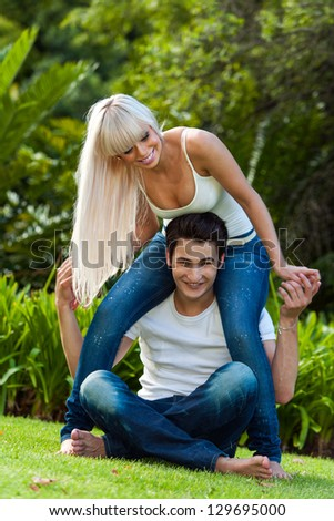 Portrait of Cute couple fooling around in park. - stock photo