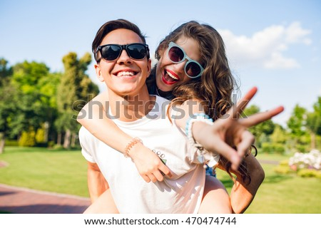 Portrait of cute couple having fun in park. Pretty girl with long curly hair is riding on back of handsome guy. They wear sunglasses and smile to camera.